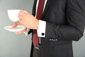 Man in black suit drinking coffee on grey background