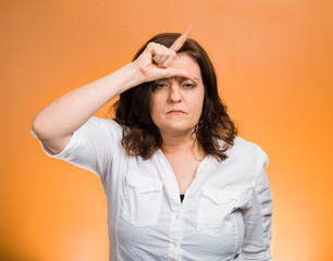 Middle aged giving loser hand gesture on orange background