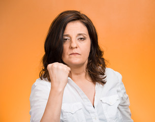 angry woman putting up showing fist warning you to stay away