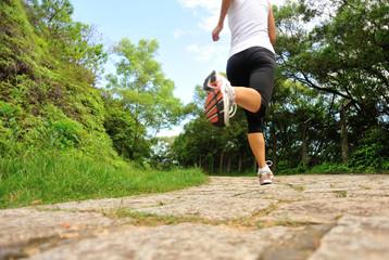 fitness woman runner legs running on stone trail