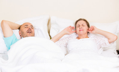 Snoring man, frustrated annoyed woman sleeping in a bed