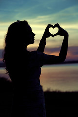 Woman's silhouette making the heart gesture