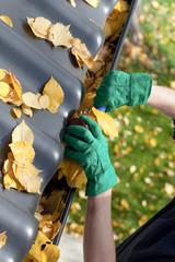 Gardener fixing rain gutter