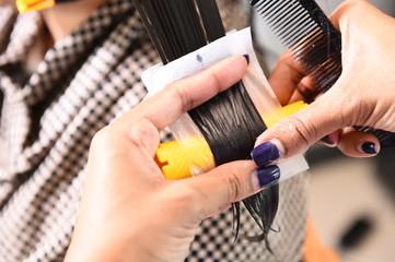 Hairdresser - hair stylist curling hairs