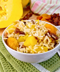 Pilaf fruit with pumpkin in bowl on board