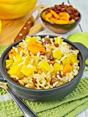 Pilaf fruit with pumpkin in pan on board