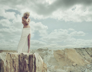 Blond lady standing on the edge of the mountain