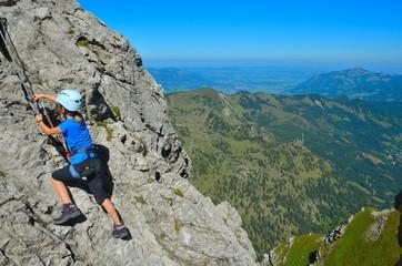 Kind beim Klettern und Sichern am Klettersteig