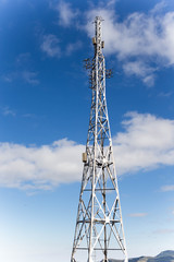 Cell phone tower over blue sky with clouds