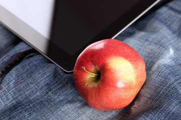 Apple and digital tablet on jeans
