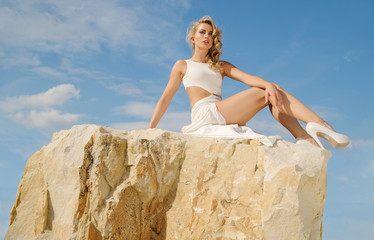 Blond girl sitting on the rocks