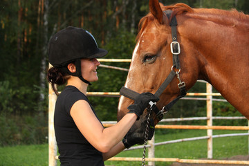 Woman in riding helmet and brown horse
