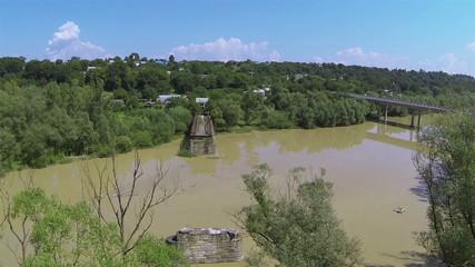Destroyed bridge through river .Aerial shot