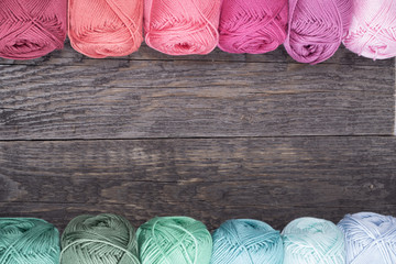 colorful yarn on wooden background close up