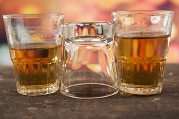 glass of rum whiskey over defocused lights background