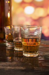 glass of rum whiskey over defocused lights background