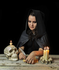 Halloween witch writing magic spell