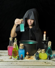 Halloween witch with magic pot and bottles