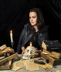 Haloween witch in black mantle with skull and ancient books