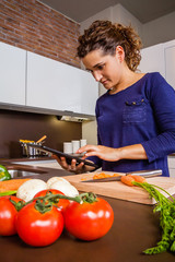 Girl in home kitchen looking recipe with a electronic tablet