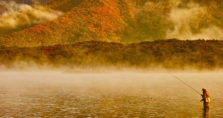 霧の中の湖と釣り人