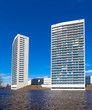 Two White Apartment Towers at the Water Front with Blue Sky