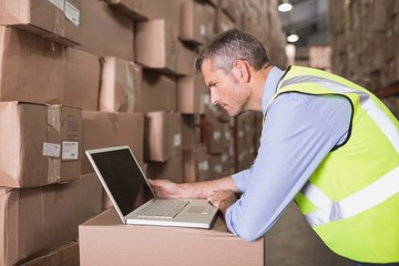Workman using laptop at warehouse