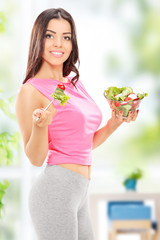 Attractive woman holding a salad at home