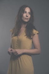 Shy brunette fashion woman wearing yellow dress. Studio shot aga