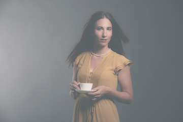 Brunette fashion woman holding white tea cup wearing yellow dres