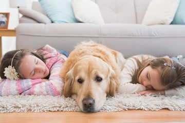 Sisters napping on rug with golden retriever
