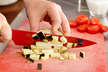 chef cutting eggplant little cubes over red chopping board