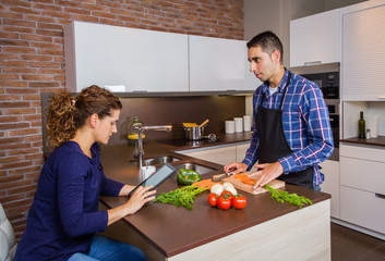 Man cooking and woman looking recipe in electronic tablet
