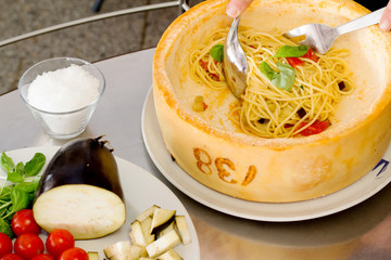 spaghetti with vegetables inside parmesan cheese wheel