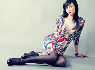 Beautiful young model with long black hair sitting on floor
