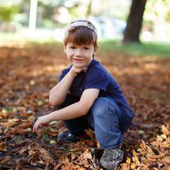 Little boy in cap posing at park