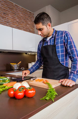 Man in home kitchen looking recipe with a electronic tablet