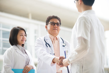 Asian medical team of doctors shaking hands inside hospital buil