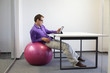 young man on stability ball working with tablet in office
