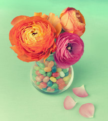 Three  beautiful ranunculus  in a vase full of sweets on a green