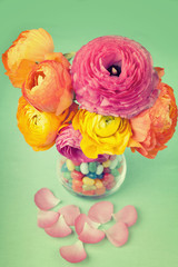 Bouquet of colorful ranunculus  in a vase full of sweets on a gr