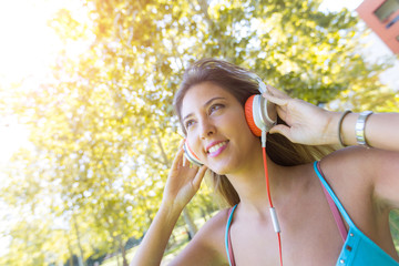 Beautiful Young Woman listening Music at Park