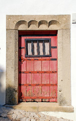 old red wooden door in white rural house, Portugal