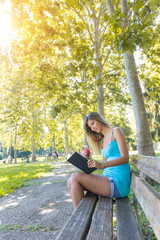 Beautiful Young Woman Reading a Book at Park