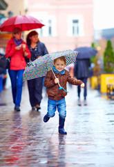 happy boy running through rainy city street