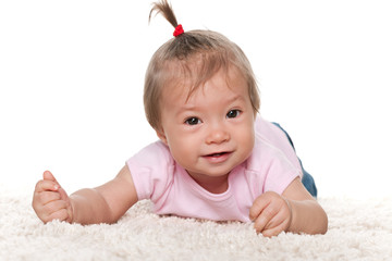 Smiling infant girl on the white carpet