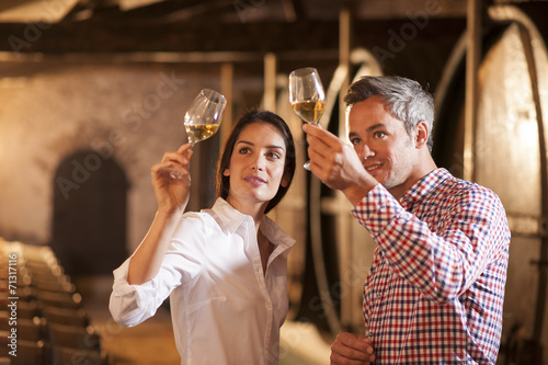 Leinwanddruck Bild Couple tasting a glass of white wine in a traditional cellar sur
