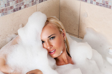 attractive woman lying in bubble bath