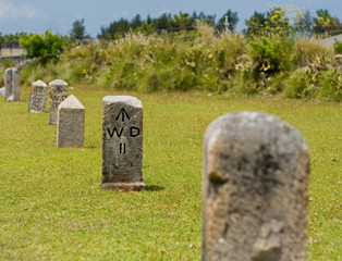 A row of stone, nautical mile markers against green grass