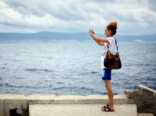 Woman at the sea taking photos